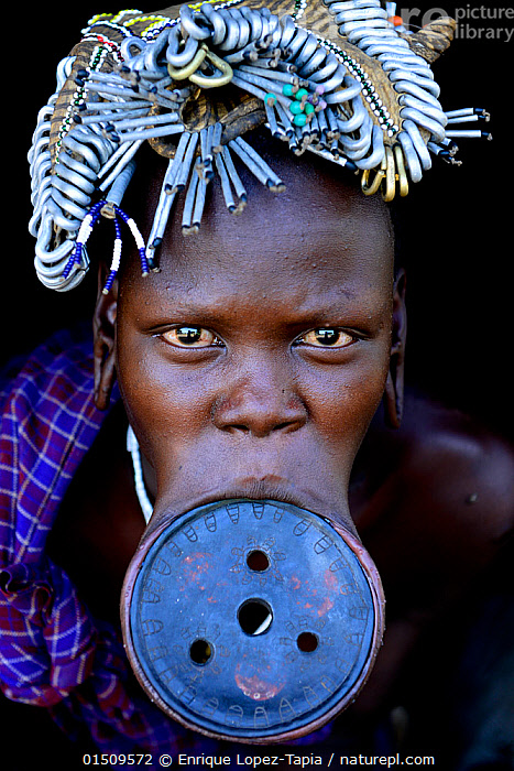 Woman with lip plate, which signifies she is a married woman, Mursi tribe, Mago National Park. Ethiopia, November 20144  ,  catalogue8,,,People,African Descent,East African Descent,Ethiopian Ethnicity,Native African Ethnicity,Woman,Only Women,One Woman Only,One Woman,Family,Life Partner,Life Partners,Wife,Wives,Marriage,Marriages,Married,Marry,1 Person,Single,Single Person,Africa,East Africa,Ethiopia,Front View,View From Front,Portrait,Mouth,Mouths,Clothing,Headdress,Outdoors,Open Air,Outside,Culture,African Culture,African,Indigenous Culture,Tribes,Direct Gaze,Native African culture,Body modification,Piercing,Stretching,Lip plate,Mursi Tribe,Mago National Park,  ,  Enrique Lopez-Tapia