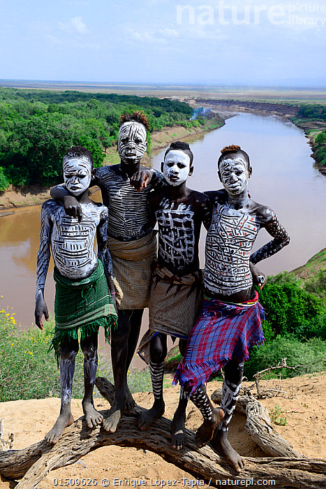 Karo boys with decorative skin painting.Territory of the Karo tribe. Omo river. Ethiopia, November 2014  ,  high15,,,Standing,People,African Descent,East African Descent,Ethiopian Ethnicity,Native African Ethnicity,Group,Group Of People,Small Group Of People,Few,4 People,Africa,East Africa,Ethiopia,Full Length,Full Lengths,Whole,Body Paint,Face Painting,Face Paintings,Horizon,Horizon Over Land,Horizons Over Land,Flowing Water,River,Landscape,Landscapes,Outdoors,Open Air,Outside,Day,Culture,African Culture,African,Indigenous Culture,Freshwater,Water,Tribes,Direct Gaze,Facepaint,Native African culture,Arm around,Omo River,  ,  Enrique Lopez-Tapia