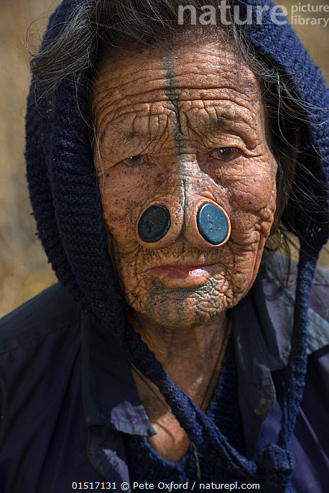 Apatani woman with facial tattoos and traditional cane nose plugs / Yapin Hulo made to make them look unattractive to males from other tribes. These facial modifications are  now  outlawed. Apatani Tribe, Ziro Valley, Himalayan Foothills, Arunachal Pradesh.North East India, November 2014., high15,,,People,Asian Ethnicity,Asian,Asians,Indian Ethnicity,Indian,Adult,Adults,Senior Adult,Woman,Traditional,1 Person,Single,Single Person,Wrinkled,Wrinkle,Wrinkles,Asia,Indian Subcontinent,India,Portrait,Outdoors,Open Air,Outside,Day,Culture,Indigenous Culture,Tribes,Direct Gaze,Arunachal Pradesh,Body modification,Piercing,Stretching,Adornment,Nose plugs,Nose Plug,Yapin Hulo,Ziro,Apatani People,, Pete Oxford