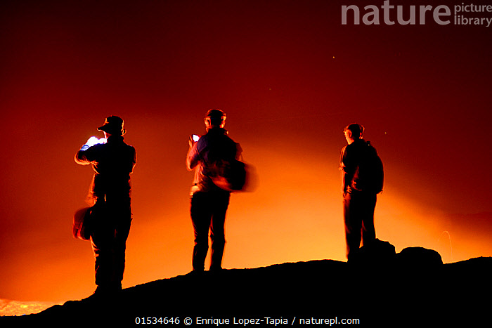 Travelers watching lava on Erta Ale volcano crater. Afar Region, Ethiopia, Africa. November 2014.  ,  Capturing An Image,Photographing,Standing,People,Man,Adventure,Spectacular,Curiosity,Colour ,Orange ,Side By Side,Group,Group Of People,Small Group Of People,Few,Luminosity,Edge,Temperature,Hot,Africa,East Africa,Ethiopia,Photography,Rear View,Back Lit,Craters,Volcano,Rock,Lava,Night,Geology,Geothermal,Hues,Active Volcano,Men,Adventures,Adventurous,Groups,Glows,Edges,Volcanoes,Volcanos,Rocks,Colours,Colors,Nights, catalogue9  ,  Enrique Lopez-Tapia