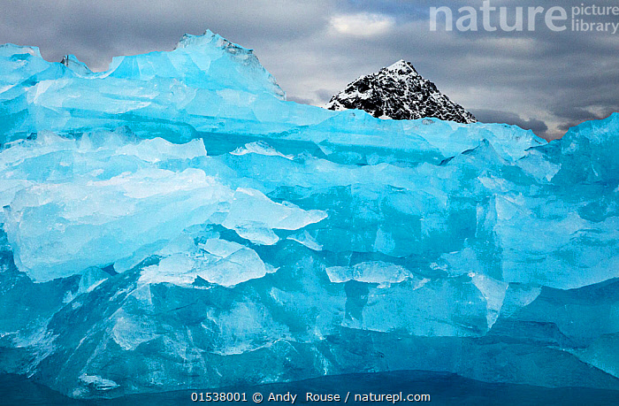Iceberg and mountain, Svalbard, Norway. Arctic. July.  ,  Arctic,Disappearing ,Disappear,Crushed,Compacted,Squashed,Colour ,Blue,Temperature,Cold,Europe,Northern Europe,North Europe,Nordic Countries,Scandinavia,Norway,Svalbard,Close Up,Mountain,Summit,Ice,Iceberg,Icebergs,Nature,Beauty In Nature,Hues,Formation,Sea ice,Submerging,Arctic,Closeups,Mountainous,Mountains,Mountain Tops,Peaks,Close-ups,Close ups,Mountain peaks,Colours,Colors,Arctic, catalogue9  ,  Andy  Rouse