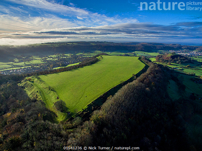 Uley Bury iron-age hill fort on Cotswold escarpment, Gloucestershire, UK. Aerial drone with CAA permit. November 2015.  ,  Sloping,Europe,Western Europe,UK,Great Britain,England,Gloucestershire,Cotswolds,Aerial View,High Angle View,Building,Military Building,Fortification,Fortifications,Fortress,Fortresses,Fort,Forts,Landscape,Landscapes,History,Woodland,Forest,Elevated view,The Past,Escarpment,Iron Age,Hill Fort,Cotswolds AONB,  ,  Nick Turner