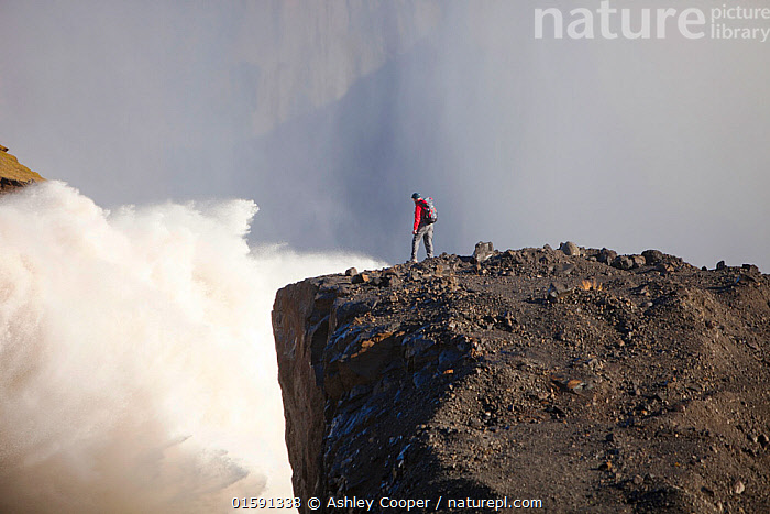 Man standing on cliff near water flowing out of the Karahnjukar dam and Halslon reservoir, a massive new controversial hydro electricity project in North East Iceland. It was created by damming the Jokuls a Dal river and flooding a large area of wilderness.  Iceland, September 2010.  ,  Iceland,Vatnajokull,Karahnjukar,wild,wilderness,hydro,HEP dam,hydro electricity,renewable energy,clean,green,carbon neutral,dam,Halslon,water power,controversial,electricity,power,energy,engineering,modern,electricity production,climate change,global warming,structure,steel,Jokuls a Dal,spill way,over flow,over spill,meltwater,water,waterfall,spray,mist,man,silhouette,,,People,  ,  Ashley Cooper