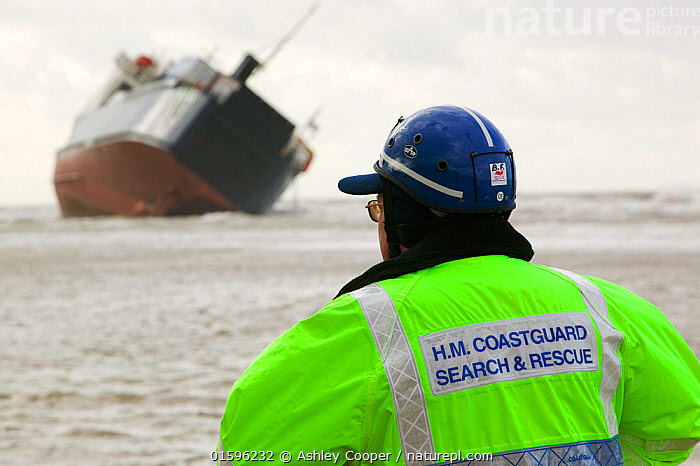 Coast guard looking at the 'Riverdance' washed ashore off Blackpool.  The 'Riverdance' was one of 3 ships lost in one day off the coast of the UK. The ship was hit by a huge wave that shifted the vehicle cargo on the decks causing the ship to list violently, England, UK. February 2008  ,  People,Man,Danger,Rescue,Rescues,Rescuing,Saving,Wreck,Shipwreck,Europe,Western Europe,UK,Great Britain,England,Lancashire,Blackpool,Boat,Weather,Storm,Bad Weather,Severe weather,  ,  Ashley Cooper