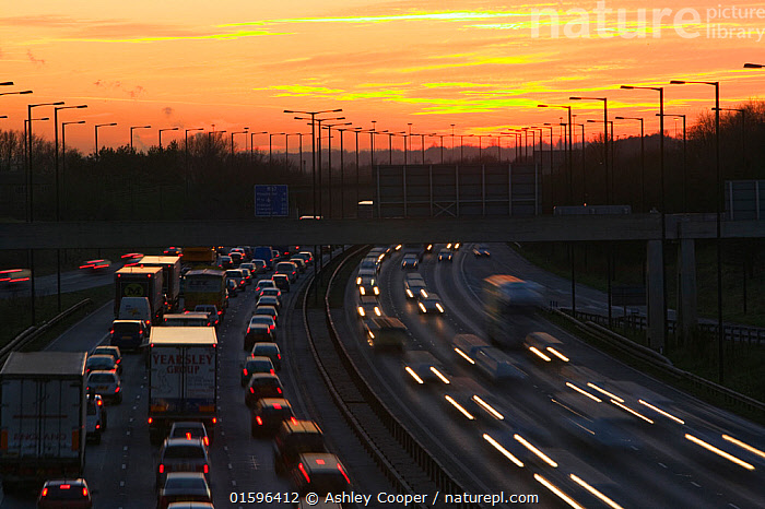 Rush hour traffic on the M60 motorway near Manchester UK. January 2007, sky,cloud,sunset,colour,colourful,red,emmissions,greenhouse gases,global warming,environmental,cost,car,travel,transport,lorry,road,motorway,M60,freeway,highway,traffic,congested,traffic congestion,gridlocked,busy,rush hour,fumes,exhaust,Manchester,England,UK,north,lanes,lamp post,dusk,twilight,dark,lights,lighting,over crowded,crowding,,,,,, catalogue11, Ashley Cooper
