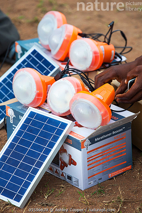 Solar lamps charging by solar panels, in the refugee camp of Chiteskesa refugee camp, near Mulanje. March 2015, Malawi,Africa,Chiteskesa,refugee camp,flood,floods,flooding,displaced,charity,NGO,aid,disaster,disaster relief,climate change,global warming,refugee,poor,poverty,light,torch,solar,solar light,renewable energy,solar panel,solar energy,efficient,charging,electricity,off grid,mobile phone,PV,photo voltaic,,,Environment,Environmental Issues,Power supply,Sustainable power,Energy,Solar power,, Ashley Cooper