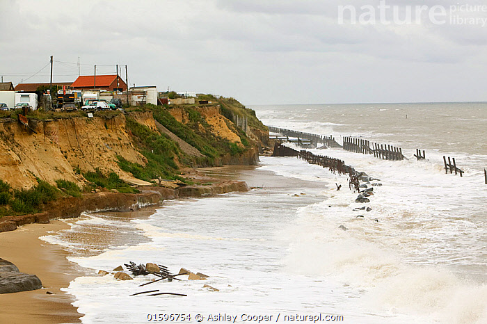 Happisburgh on the Norfolk Coast. This section of coast is the fastest eroding point in the UK and speeding up to to global warming induced sea level rise and increased stormy weather. August 2006  ,  wave,waves,crashing,violent,storm,stormy,weather,extreme weather,wind,windy,white water,breaking,defences,sea,sea defences,global warming,sea level rise,erosion,coastal erosion,glacial,till,deposits,beach,cliff,collapse,coast,Happisburgh,Norfolk,rapid erosion,breach,break down,spume,white horses,threat,vulnerable,town,dwellings,houses,close,edge,danger,dangerous,clouds,cloudy,sky,crumbling,soft,destroyed,lifeboat ramp,launch,concrete,broken up,defenceless,,,,  ,  Ashley Cooper