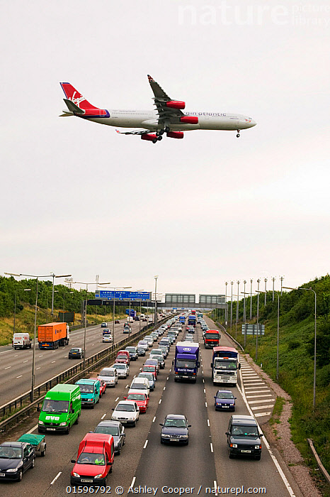 Traffic congestion on the M1 motorway at Loughborough,  with a plane coming into land at East Midlands Airport. August 2005, car,lorry,van,transport,transportation,motorway,M1,carriageway,lane,lamp,post,crash,barrier,rush,hour,slow,breaking,que,queue,delay,frustration,congestion,crawl,exhaust,fumes,pollution,atmosphere,greenhouse,gas,co2,emmissions,carbon,global,warming,plane,jet,landing,airport,East midlands airport,,,,, Ashley Cooper