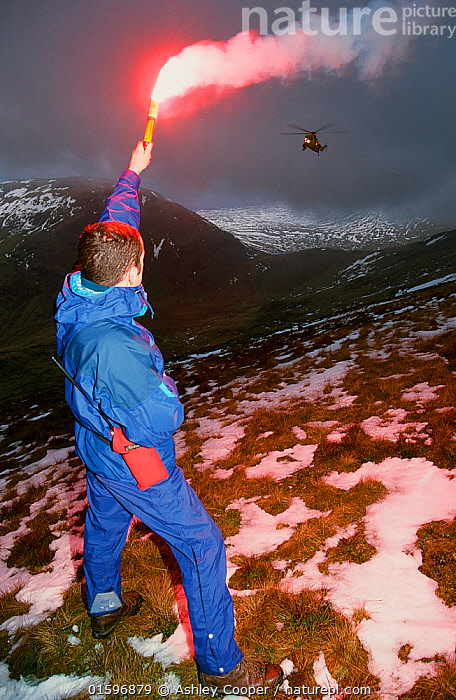 A mountain rescue member uses a flare to attract an approaching sea king helicopter to the casualty site on Fairfield, Lake District, England, UK., Lake,district,National,Park,Cumbria,UK,mountain,rescue,team,Langdale,Ambleside,Rescue,Team,emergency,help,asssist,assistance,brave,selfless,volunteer,climber,climbing,hill,walking,terrain,risk,,,People,,, catalogue11, Ashley Cooper