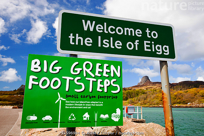 Big green Footsteps sign on Eigg Harbour, Scotland, UK. May 2012, Eigg,island,Scotland,UK,Eigg Heritage Trust,community,energy,power,electric,electricity,renewable,renewable energy,renewable power,wind power,solar power,hydro,hydro power,clean,green,zero emissions,climate change,global warming,carbon footprint,feed in tariff,future,Eigg electric,self sufficient,self sufficiency,sign,welcome,big,footsteps,statement,pride,lifestyle,environment,eco,peak,An Sgurr,promontary,prow,icon,,,,, Ashley Cooper