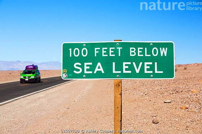 Sign at 100 feet below sea level in Death Valley. Death Valley is the lowest, hottest, driest place in the USA, with an average annual rainfall of around 2 inches, some years it does not receive any rain at all. Death Valley, California, USA. October 2014.  ,  California,USA,America,Death Valley,desert,drought,hot,dry,low,heat,National Park,preserved,protected,mud cracks,lake bed,dessicated,barren,mountain,mountain range,geology,rocks,sand,sandy,road,sign,green,100 fett,below sea level,sea level,van,truck,,,,  ,  Ashley Cooper