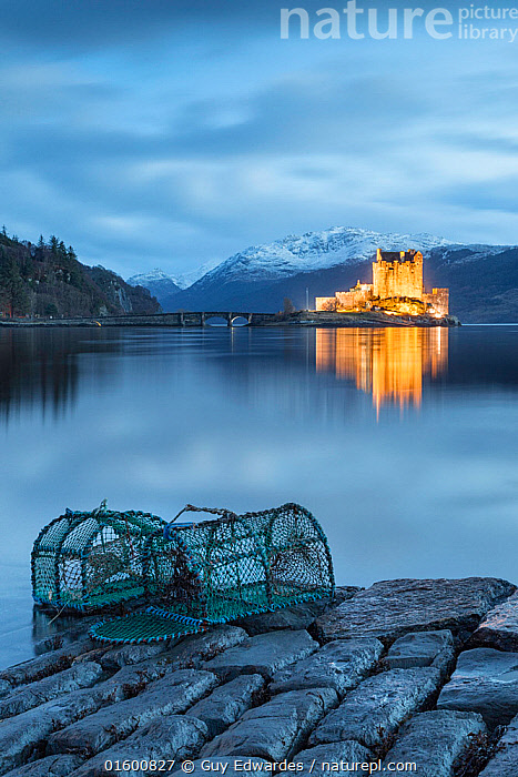 Lobster pots at edge of Loch Duich, Eilean Donan Castle in background. Highlands, Scotland, UK. January 2014.  ,  Mood,Calm,Luminosity,Illuminated,Illuminating,Illumination,Illuminations,Iluminated,Europe,Western Europe,UK,Great Britain,Scotland,Highland,Equipment,Fishing Equipment,Lobster Trap,Lobster Pot,Lobster Pots,Lobster Traps,Building,Historic Building,Castle,Castles,Paving,Paved,Cobble,Cobbled,Cobbles,Cobblestone,Cobblestones,Mountain,Reflection,Sky,Cloud,Weather,Overcast,Landscape,Freshwater,Lake,Water,Fishing,Highlands of Scotland,Loch,,, catalogue11  ,  Guy Edwardes