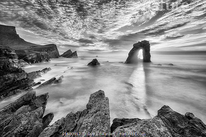 Gaada Stack, Foula, Shetland, Scotland, UK. August, 2016.  ,  Erosion,Sayings,Light At The End Of The Tunnel,A Light At The End Of The Tunnel,Europe,Western Europe,UK,Great Britain,Scotland,Shetland,B/W,Monochromatic,Photographic Effect,Long Exposure,Cliff,Rock Formations,Arch,Arches,Hole,Rock,Sky,Cloud,Ocean,Atlantic Ocean,Wave,Landscape,Coast,Marine,Coastal,Water,Geology,Saltwater,Sea,North Sea,Rocky,Landform,  ,  Guy Edwardes