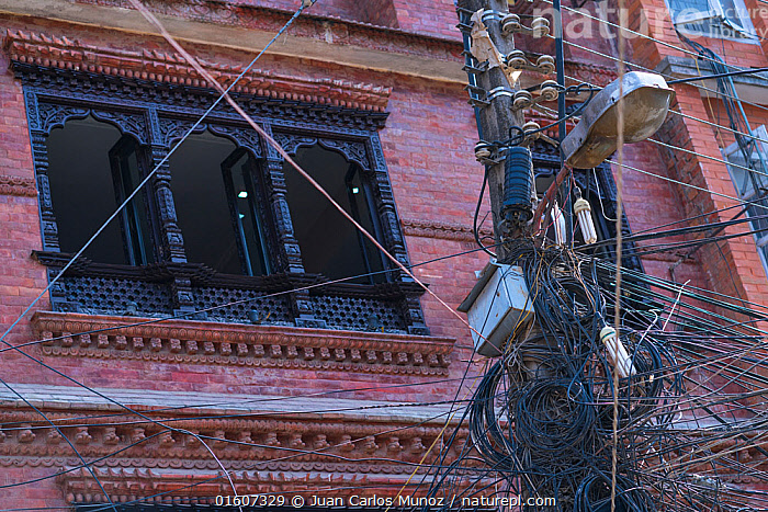 Cables and telegraph pole with building in background, Kathmandu City, Kathmandu Valley, Nepal. February 2018., Group,Large Group,Asia,Indian Subcontinent,Nepal,Kathmandu,Katmandu,Artifical light,Electric Light,Street Light,Utility Pole,Telephone Pole,Building,Window,Wire,Overhead cables,Electrical Wire,Telegraph Wire,, Juan  Carlos Munoz