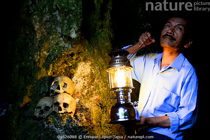 Man with lantern lighting up skulls on rock at Toraja cemetery. The Toraja culture of West and South Sulawesi revolves around death with funeral ceremonies an important part of daily life. Indonesia. 2015., People,Asian Ethnicity,Asian,Asians,Man,Few,Three,Group,Dark,Asia,South East Asia,Indonesia,Bone,Bones,Skull,Skulls,Artifical light,Lantern,Lanterns,Cemetery,Rock,Religion,Death,Biodiversity hotspot,Sulawesi,Wallacea,Indonesian Ethnicity,Toraja,, Enrique Lopez-Tapia