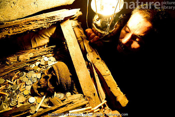 Man looking at skull, coins and cigarettes in cave, Toraja cemetery. The Toraja culture of West and South Sulawesi revolves around death with funeral ceremonies an important part of daily life. Indonesia. 2015., People,Asian Ethnicity,Asian,Asians,Man,Dead,Dark,Asia,South East Asia,Indonesia,Bone,Bones,Skull,Skulls,Artifical light,Electric Light,Lantern,Lanterns,Money,Cash,Coin,Coins,Tobacco Product,Cigarette,Cigarettes,Cemetery,Culture,Death,Biodiversity hotspot,Sulawesi,Wallacea,Observing,South Sulawesi,Indonesian Ethnicity,Toraja,Tana Toraja,, Enrique Lopez-Tapia