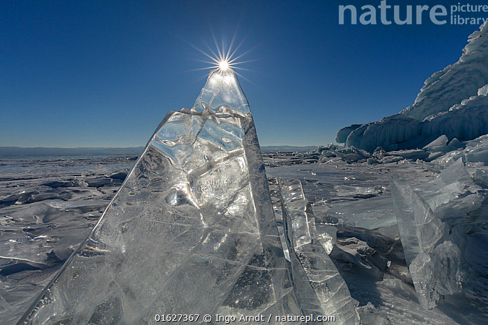 Sun rising over ice formations on Lake Baikal. Siberia, Russia. February 2019.  ,  Frozen,Russia,Siberia,Sunlight,Light Ray,Sky,Ice,Sunrise,Landscape,Winter,Water Surface,Water,Protected area,UNESCO World Heritage Site,Dawn,Lake Baikal,Blue sky,Natural Light,Translucent,Siberian Federal District,North Asia,Asian Russia,  ,  Ingo Arndt