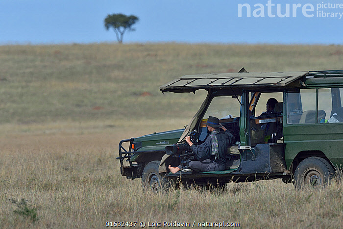 Camerawoman waiting in vehicle, looking out over the savanna, Masai Mara, Kenya. March.  ,  Capturing An Image,Filming,People,Woman,Camera Operators,Cameramen,Africa,East Africa,Kenya,Equipment,Photographic Equipment,Camera,Video Camera,Video Cameras,Movie Camera,Film Camera,Film Cameras,Movie Cameras,Land Vehicle,Savanna,Wildlife watching,Safari,camerawoman,  ,  Loic Poidevin