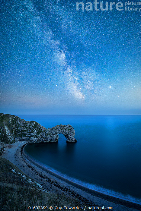 Milky Way above Durdle Door rock arch. Jurasic Coast, Dorset, England, UK. August 2019. Composite image.  ,  Catalogue13,Europe,Western Europe,UK,Great Britain,England,Dorset,Composite Image,Composite Images,Digital Composite,Photographic Effect,Long Exposure,Rock Formations,Arch,Arches,Outer Space,The Universe,Galaxy,Galaxies,Stars,Sky,English Channel,The English Channel,Landscape,Coast,Marine,Coastal,Water,Geology,Saltwater,Sea,Jurassic Coast,UNESCO World Heritage Site,Milky Way,night sky,Landform,Catalogue13,Coastlines,Skies,Landscapes,Coasts,Seas  ,  Guy Edwardes