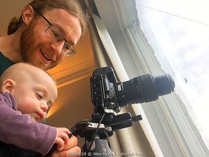 Photographer Alex Hyde working from home whilst carrying baby daughter during the Covid-19 Pandemic, April 2020  ,  Capturing An Image,Photographing,People,Child,Baby,Babies,Infancy,Infant,Infants,Man,Photographer,Photographers,Cute,Adorable,Europe,Western Europe,UK,Great Britain,England,Photography,Indoors,Reserve,Protected area,National Park,Young,Young Person,Covid lockdown,  ,  Alex Hyde