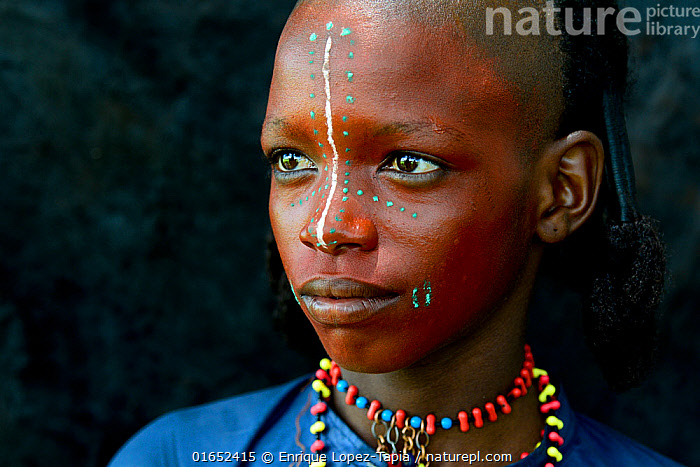 Boy from Wodaabe nomadic tribe with painted face, portrait. During Gerewol celebration, a gathering of different clans in which women choose a husband. Chad, Sahel, Africa. 2019.  ,  People,African Descent,Native African Ethnicity,Wodaabe,Wodaabe Tribe,Wodaabes,Celebration,Celebrate,Celebrating,Celebrations,Traditional,Africa,Central Africa,Chad,Portrait,Body Paint,Face Painting,Face Paintings,Clothing,Desert,Sahara Desert,Sahara,Sahel,Sahal,Sahal Desert,Sahel Desert,Sahil,Sahil Desert,Facepaint,Fula,Fulani,Fulah,Peul,Peulh,Peuhl,  ,  Enrique Lopez-Tapia