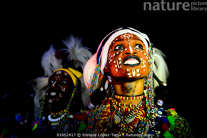 Two men from Wodaabe ethnic group dancing and singing with painted faces during Gerewol celebration, a gathering of different clans in which women choose a husband. Chad, Sahel, Africa. 2019.  ,  People,African Descent,Native African Ethnicity,Wodaabe,Wodaabe Tribe,Wodaabes,Celebration,Celebrate,Celebrating,Celebrations,Traditional,Two,Africa,Central Africa,Chad,Body Paint,Face Painting,Face Paintings,Clothing,Traditional Clothing,Desert,Sahara Desert,Sahara,Sahel,Sahal,Sahal Desert,Sahel Desert,Sahil,Sahil Desert,Facepaint,Fula,Fulani,Fulah,Peul,Peulh,Peuhl,  ,  Enrique Lopez-Tapia