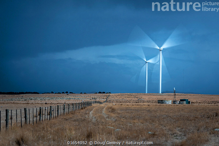 Two wind turbines with blades rotating, grassland in foreground. Mount Gellibrand Wind Farm, Victoria, Australia. March 2019.  ,  Spinning,Spin,Two,Australasia,Australia,Victoria,Equipment,Power Equipment,Turbine,Wind Turbine,Infrastructure,Energy Infrastructure,Energy Infrastructures,Wind Farm,Wind Farms,Landscape,Environment,Environmental Issues,Power supply,Renewable Energy,Energy,Moving,Movement,  ,  Doug Gimesy