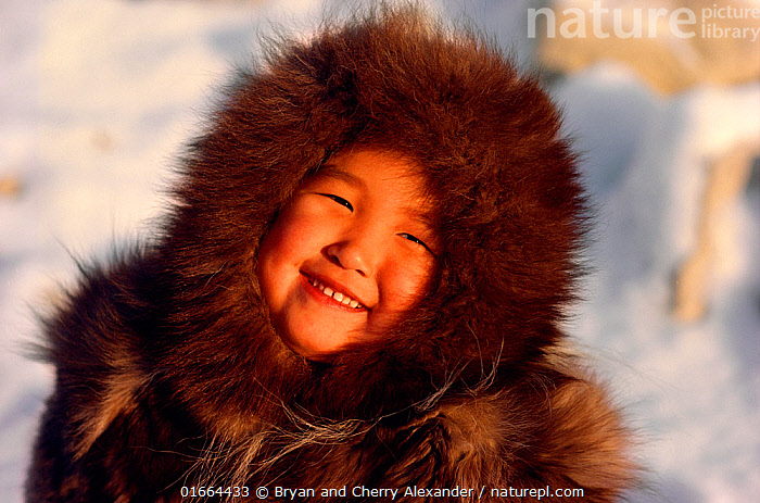 An Inuit girl, Sofie, warmly dressed in a fox fur hooded jacket (kapataq). N.W. Greenland. 1987  ,  People,Inuit,Eskimo,Eskimoes,Eskimos,Innuits,Inuits,Child,Happiness,Facial Expression,Smiling,Arctic,Polar,Portrait,Clothing,Traditional Clothing,Warm Clothing,Warm Clothes,Winter Clothes,Winter Clothing,Season,Winter,Culture,Indigenous Culture,Tribes,Arctic people,Kalaallit Nunaat,Young,Young Person,  ,  Bryan and Cherry Alexander