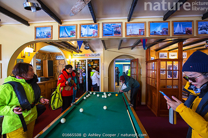 Tourists from expedition cruise ship playing at billiards table and purchasing postcards in shop. Vernadsky Station Ukranian research base, Galindez Island, Argentine Islands, Antarctica. 2019.  ,  Leisure,People,Tourist,Tourists,Antarctica,Antarctic,Polar,Equipment,Leisure Games,Billiards,Games Equipment,Billiard Table,Billiard Tables,Snooker Table,Snooker Tables,Sports Equipment,Sport Equipment,Pool Table,Pool Tables,Building,Place Of Research,Research Facility,Research Facilities,Indoors,Travel,Tourism,Wilhelm Archipelago,Argentine Islands,Galindez Island,  ,  Ashley Cooper