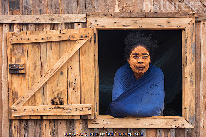 Local woman with Sandalwood paste decoration on face, South Madagascar. November 2018.  ,  People,Woman,Africa,Madagascar,Malagasy Republic,Republic of Madagascar,Portrait,Decoration,Cosmetics,Cosmetic,Make-Up,Makeup,Building,Window,Biodiversity hotspots,Biodiversity hotspot,Local people,  ,  Pete Oxford