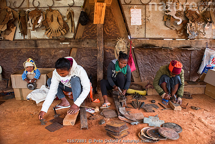 Deaf workers, in metal factory, making metal artefacts for tourist industry, Antananarivo, Madagascar. October 2018.  ,  Working,People,Manual Worker,Metal Worker,Metal Workers,Disabled,Physical Impairment,Deaf,Deafness,Hard Of Hearing,Africa,Madagascar,Malagasy Republic,Republic of Madagascar,Building,Industrial Building,Industrial Facility,Factory,Metalic,Metals,Biodiversity hotspots,Biodiversity hotspot,Local people,  ,  Pete Oxford