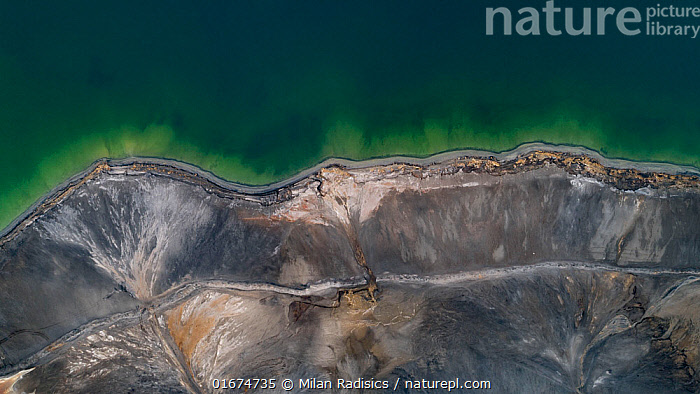 Aerial view of ash pond near Turek, Poland. Former open pit coal mine now used to store coal ash after burning in power plants. The ash is mixed with water and pumped through a pipeline into the ash pond. The vivid green colour indicates the presence of calcium carbonate used to neutralise the acidic wastewater. Although this site is nicknamed 'The Polish Maldives', the attractive-looking water is actually toxic wate. Ash ponds can contaminate the environment with pollutants harmful to human health.  ,  Toxic Waste,Toxic Wastes,Colour,Green,Waste,Pollution,Europe,Eastern Europe,East Europe,Poland,Aerial View,High Angle View,Directly Above,Overhead,Unusual Angle,Chemical,Chemicals,Substance,Ash,Ashes,Fossil Fuel,Mineral,Minerals,Environment,Environmental Issues,Global Warming,Greenhouse Effect,Environmental Damage,Power supply,Industry,Arty shots,Abstract,Abstracts,Energy,Climate change,Elevated view,Thermal,Drone,Drone shot,Carbon Emission,Coal,Ash pond,Carbon emissions,  ,  Milan Radisics