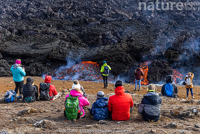 Icelandic people watching and photographing the lava at the eruption site of the Fagradalsfjall volcano, Iceland. 5 April 2021  ,  Iceland,,,Erupting,People,Europe,Northern Europe,North Europe,Nordic Countries,Scandinavia,Iceland,Volcano,Lava,Travel,Tourism,Geology,Volcanic features,Lava flow,  ,  Theo  Bosboom