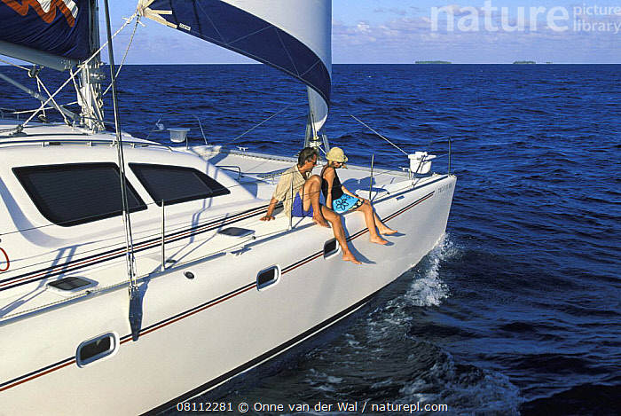 Two people sitting on the edge of a cruising catamaran, Belize., CARIBBEAN,CATAMARANS,CENTRAL AMERICA,COASTS,COUPLES,CREWS,CRUISING,ISLANDS,LIFESTYLES,PEACEFUL,ROMANTIC,SAILING BOATS,SITTING,VCATIONS,YACHTS,YOUNG,West Indies,Concepts,BOATS, Onne van der Wal