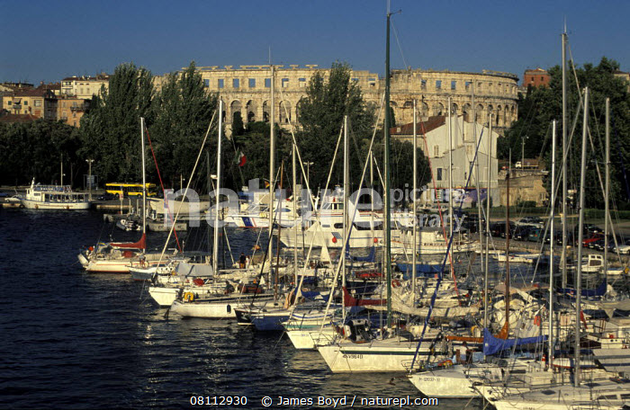 Boats moored in marina with amphitheatre in the background, Pula, Slovenia.  ,  BALKANS,BOATS,BUILDINGS,EUROPE,HARBOURS,HISTORICAL,MARINAS,MEDITERRANEAN,MOORED,SAILING BOATS,YACHTS  ,  James Boyd