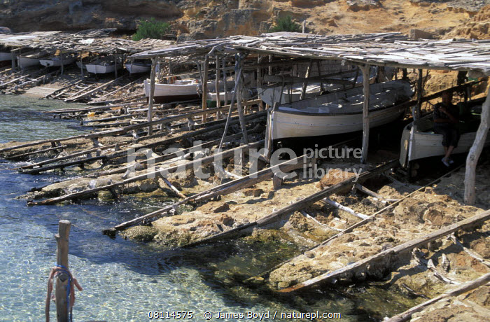 Fishing boats under shelters, Ibiza.  ,  BALEARIC ISLANDS,BOATS,COASTS,DRY LAND,EUROPE,FISHING BOATS,MEDITERRANEAN,SLIPWAYS,TRADITIONAL,WOODEN, WORKING-BOATS  ,  James Boyd