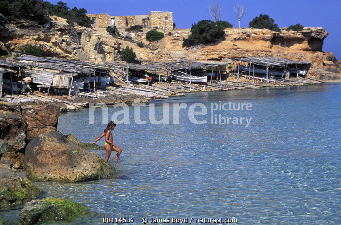 A young girl paddling in a shallow bay, with traditional fishing boats in beach shelters, Formentera Island, Ibiza  ,  ALONE,BALEARIC ISLANDS,BOATS,CHILDREN,COASTS,EUROPE,HOLIDAYS,MEDITERRANEAN,PADDLING,ROCKS,SPAIN,CONCEPTS  ,  James Boyd