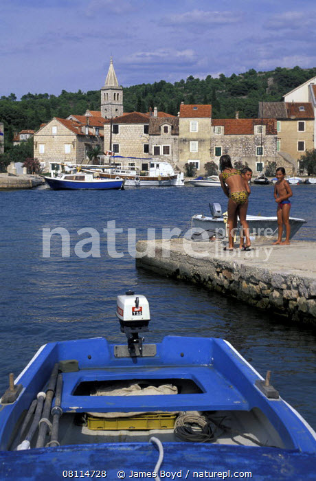 Children playing on the jetty in a small harbour on the island of Zlarin, Croatia.  ,  VERTICAL,BOATS,BUILDINGS,CHILDREN,COASTS,CROATIA,EUROPE,HARBOURS,MEDITERRANEAN,PEOPLE,PLAYING,TENDERS,TOWNS, OPEN-BOATS  , OPEN-BOATS  ,  James Boyd