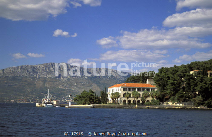 Villa standing on the coastline with rugged mountain beyond, Croatia.  ,  BOATS,BUILDINGS,CLIFFS,COASTS,CROATIA,EASTERN EUROPE,EUROPE,LANDSCAPES,MEDITERRANEAN,MOUNTAINS,Geology  ,  James Boyd
