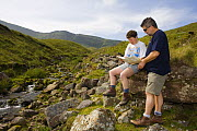 Walkers reading map at Llyn y Fan Fach, Brecon Beacons National Park, Powys, Wales  -  Nick Turner