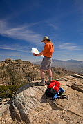 Hiker looking at map, in Finger Rock Canyon on the Mount Kimball Trail part of the Pusch Ridge Wilderness of Coronado National Forest, USA, March 2009, model released  -  Kirkendall-Spring