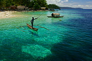 View of beach, and man fishing from a dugout canoe, at Yenbeser Village. Alfred Russel Wallace based himself in this village for several months in the 1850's. Raja Ampat Islands, Indonesia. May 2007 - Tim Laman