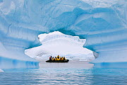 Zodiac filled with tourists seen through ice arch in an iceberg, Pleneau Island, Antarctica, February 2009.  -  Bryan and Cherry Alexander