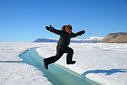 Young Inuit boy jumping over a crack on ice floe, Ellesmere Island, Nanavut, Canada, June 2012. Model released. - Eric Baccega