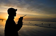 Shark spotter looking out to sea at Muizenberg Beach at sunset, near Cape Town, Western Cape, South Africa. July 2013. - Cheryl-Samantha  Owen