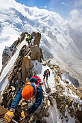 Mont Blanc with climbers on the Cosmiques Arete, climbing the ladder to access the cable car station. Aiguille Du Midi above Chamonix, France, September 2014 - Ashley Cooper