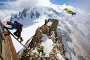 Climbers on the Cosmiques Arete, climbing the ladder to access the cable car station, and a base jumper in a wing suite flying past. Mont Blanc from the Aiguille Du Midi above Chamonix, France, Septem... - Ashley Cooper
