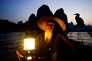 Traditional Chinese fisherman holding lantern / light on raft at dusk with domesticated Cormorant (Phalacrocorax carbo sinensis) used to catch fish, Karst peaks in background. Li River, Yangshuo, Guan...  -  Enrique Lopez-Tapia