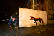 Photographer Matt Maran testing remote camera for a planned shot to capture a Red fox (Vulpes vulpes) next to a stencil by Stewy Stencils North London, England, UK. March 2018.